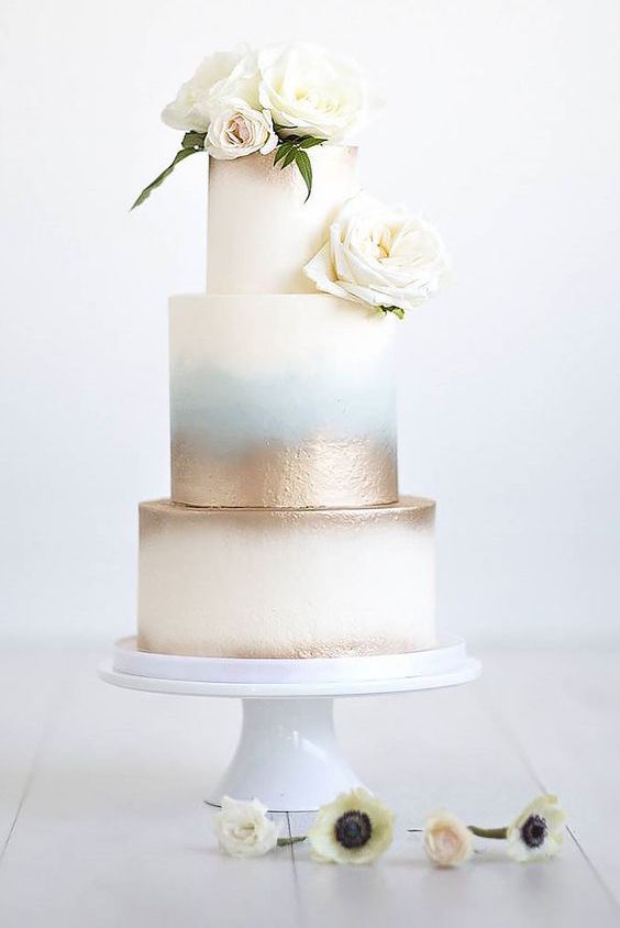 These simple delicate romantic wedding cakes are very stylish. 3 perfectly smooth tiers with a touch of blue and gold.