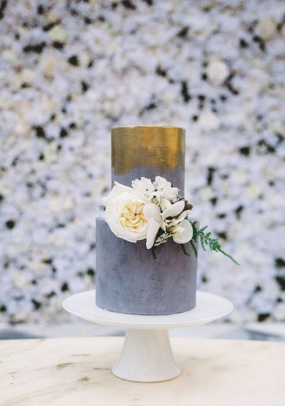 This wedding cake from Sweet Bakes boasts modern elegance with its golden pattern and clean lines.