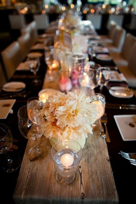Black and gold wedding table with a wood beam as a table runner. Talk about glamming up the place!