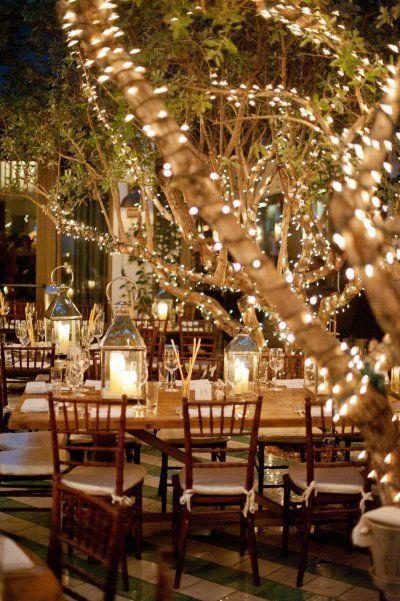 Boda al aire libre iluminada por velas y luces navideñas y faroles.