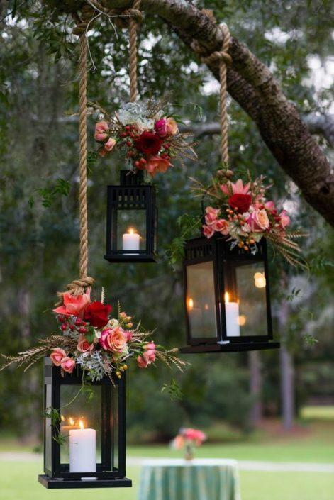 Faroles para bodas colgantes con flores en rosa para la decoración de tu recepción. Fotografía: Hopkins Studios.