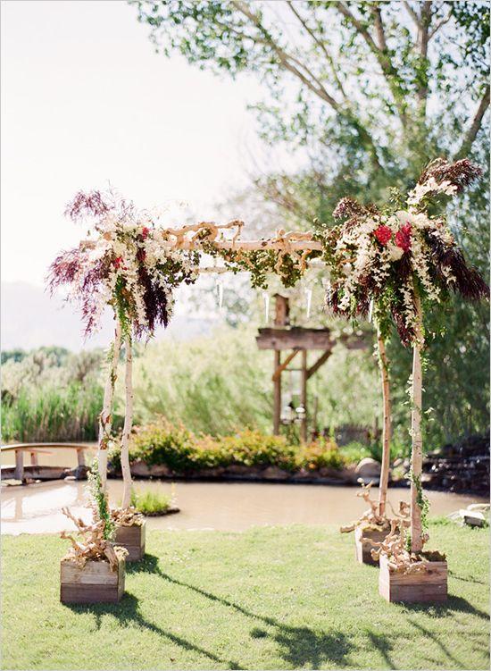 Preciosa decoración de flores en este arco de abedul o birch.