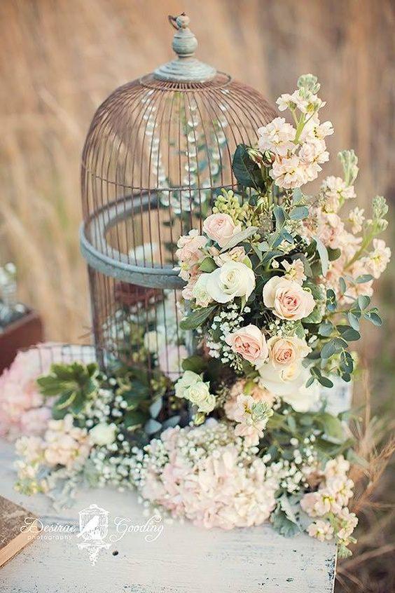 Una jaula de pájaros puede tener muchos usos en una boda. Esta desborda de flores. Delicado y romántico centro de mesa.
