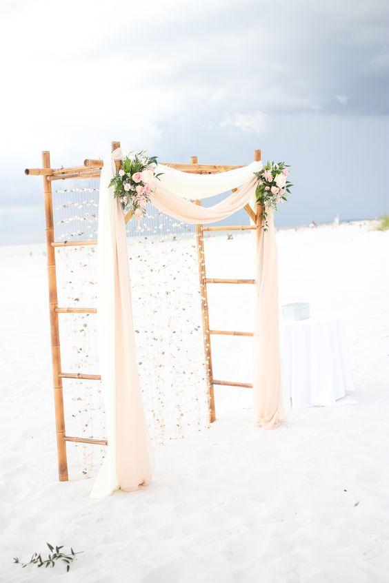 Rústico y romántico arco de bambú con una cortina de conchillas, perfecta para una boda en la playa.