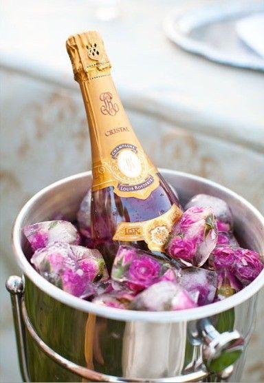 Champagne helada en una cubeta llena de cubos de hielo con rosas.