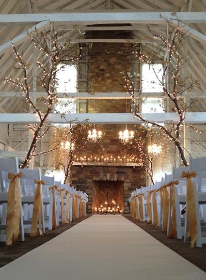 Stunning wedding venue made with tree decorations; fairy lights and fireplace focal point using wood and stones.