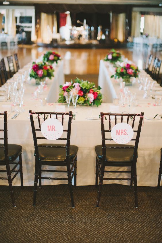 U-shaped head table layout with personalized signs hung on the bride's and groom's chairs.