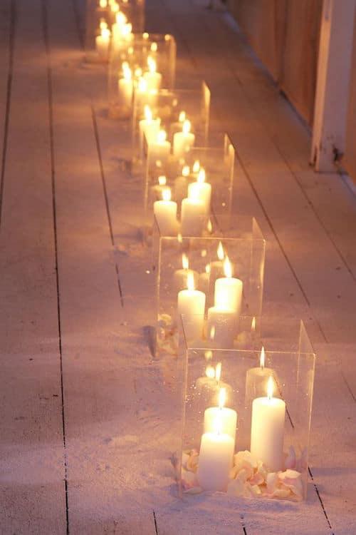 Las luces de las velas se multiplican en el vidrio del portavelas.. Una idea hermosa y romántica...