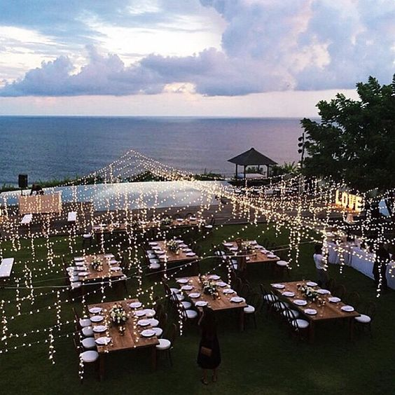 Amazing lighting canopy above a perfect seating layout on this Bali wedding. The head table at the top facing the long rectangular tables for the guests provides ample circulation space between them.