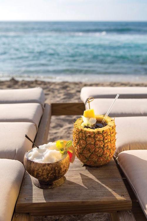 Disfruta unos tragos con piña y coco en la playa.