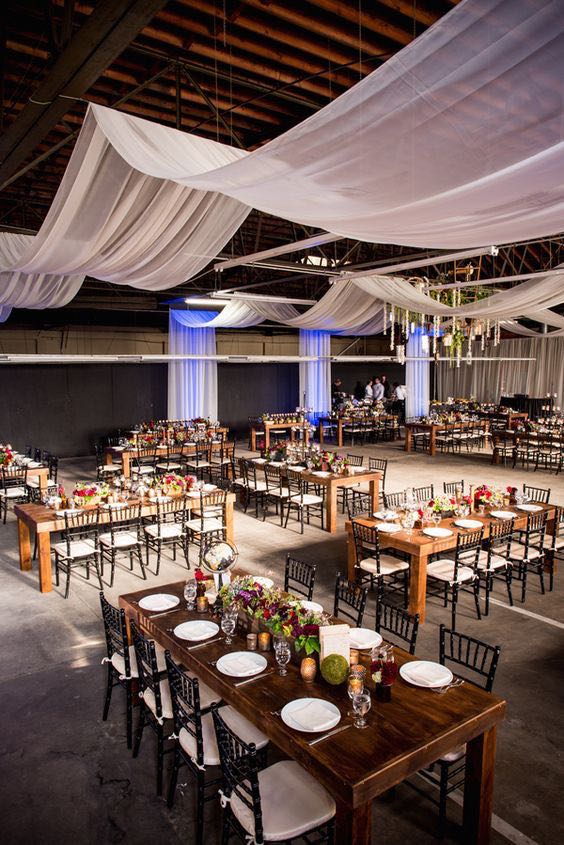 Long rectangular tables in a warehouse wedding reception.