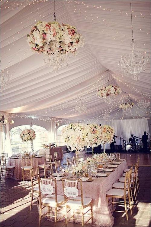 Carpa para bodas de lujo con chandelier cubierto de flores.