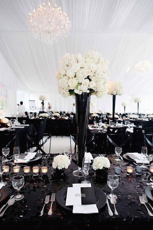 Centros de mesa altos en negro y blanco sobre un pasillo central de lino con lentejuelas. Fotografía Kortnee Kate.