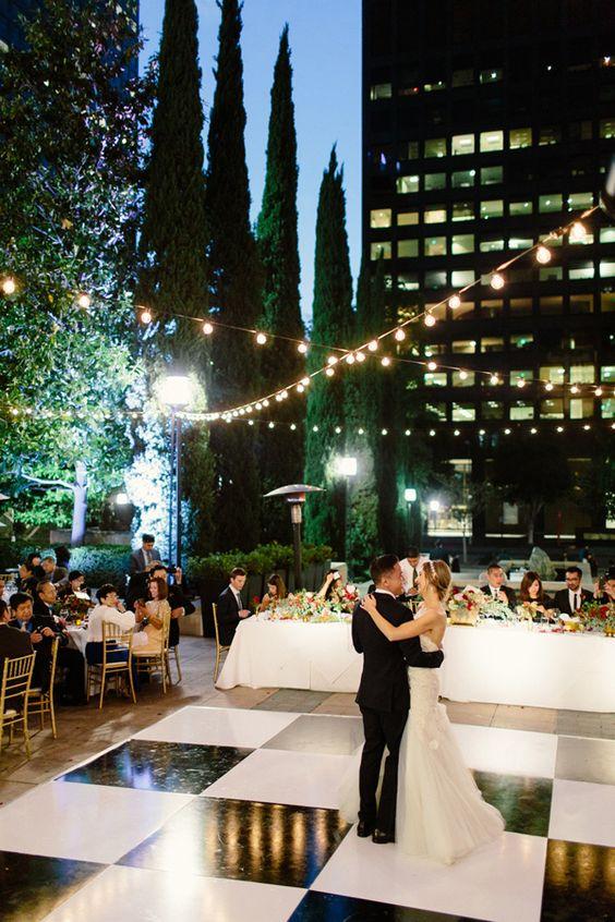 Boda en una terraza en downtown Los Angeles estilo Gatsby llena de luces. City rooftop wedding reception in downtown Los Angeles Gatsby style with twinkle lights. Fotografía The Melideos.