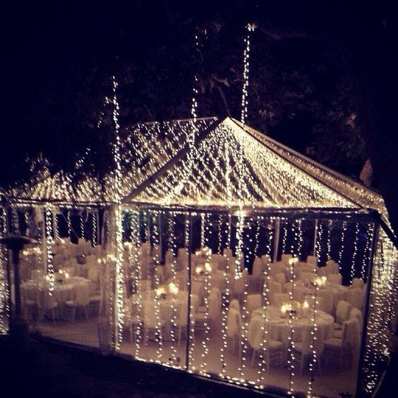 Una boda de noche con una carpa cónica transparente envuelta en luces de navidad.