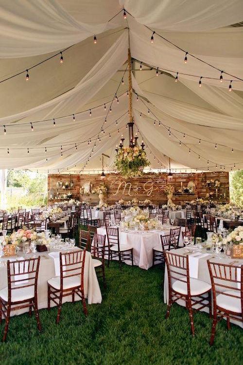 Una recepción de boda bajo una carpa en el patio de casa.