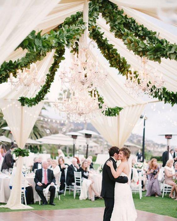 Decora una carpa para fiestas abierta, con arañas y guirnaldas de enredaderas para una boda romántica. Amber Event Production.