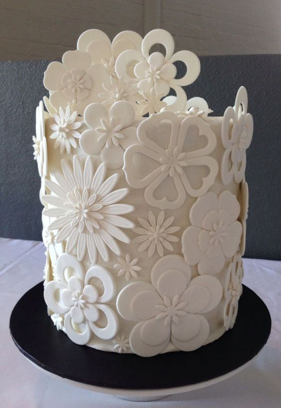 Very modern yet classic white cut out flower wedding cake. Created by Pamela McCaffrey.