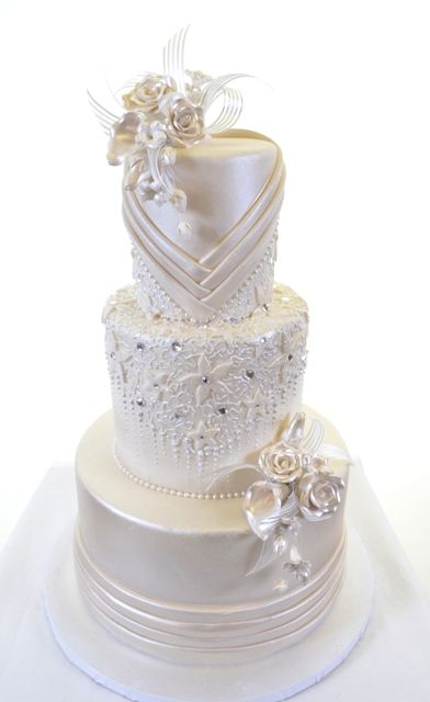 Three sparkling white round tiers form an achromatic tower then decked out in pintucks encircling the bottom layer forming a V on the top layer. A strand of pearls outlines the pintucks marking the start of an intricate lace at the very top. Created by Pastry Palace, Las Vegas.