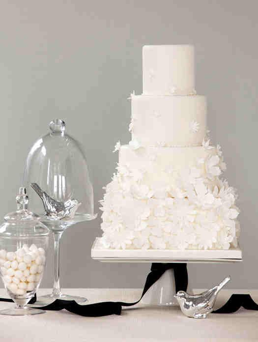 A traditional white wedding cake with a gorgeous flowery design.
