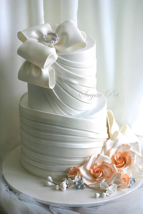 Contemporary wedding cake surrounded with giant blush flowers by Sugar Pot.