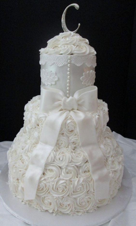 This white wedding cake matches the color and design of the bridal gown.
