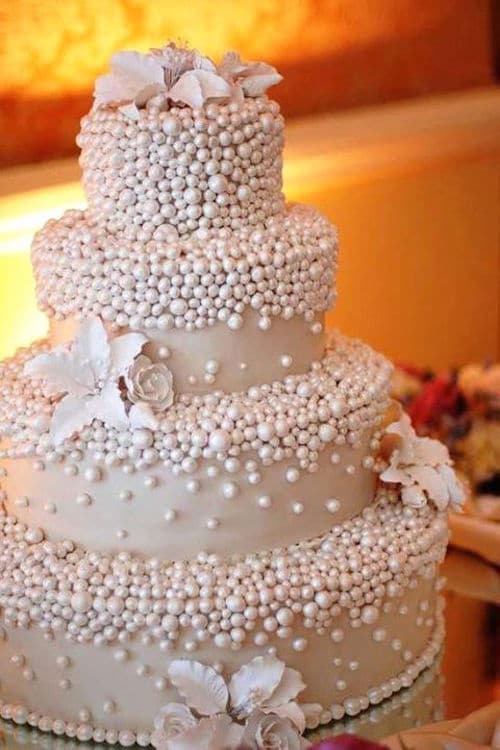 Four tiers of white wedding cake deliciousness showered in pearls.