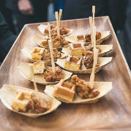 Chicken n' waffles with maple gastrique on recyclable palm leaf plates by Purslane Catering.