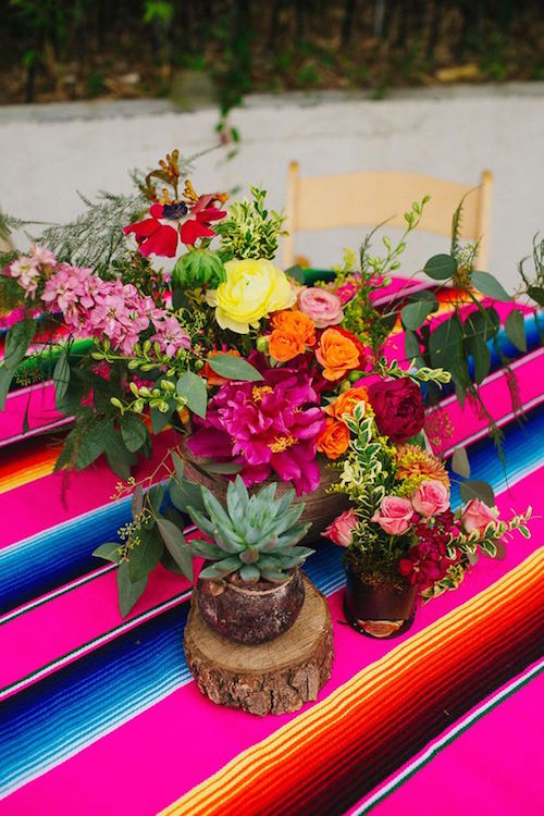 Colorful centerpieces: mix flowers and cactuses on top of a Mexican sarape. Belmont, Dallas. Photography Amber Vickery.