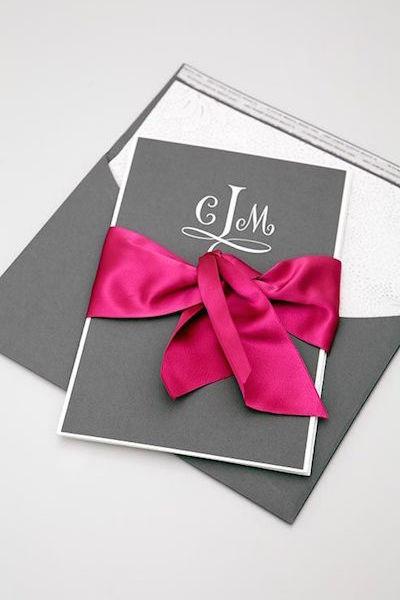 Invitaciones de boda en gris con un lazo de seda en fucsia. Un look de lujo que hará furor en el 2017. Fotografia: Colin Cowie Weddings.