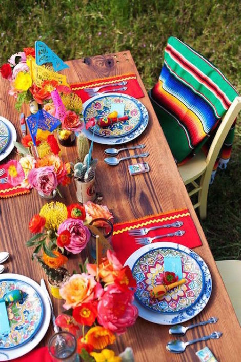 Mexican Fiesta inspired in Frida Kahlo with Sarapes, Talavera dishes, maracas, papel picado and paper flowers.