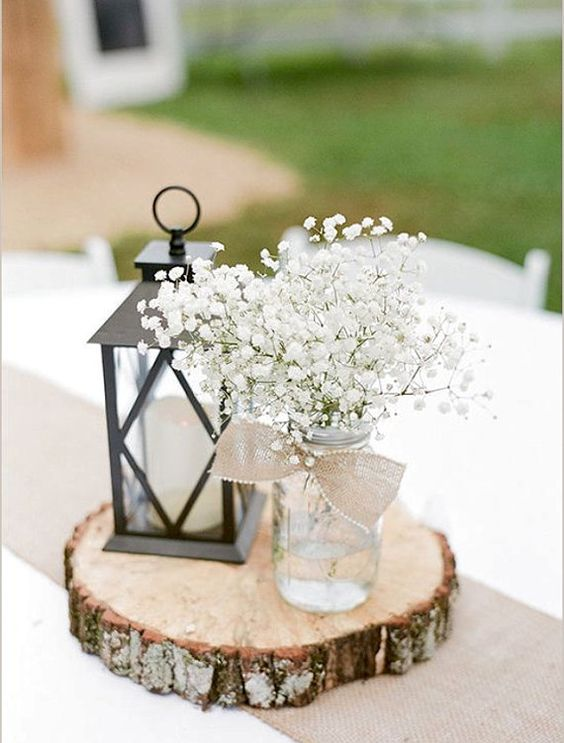 Lantern wedding centerpiece on top of round tree bark.
