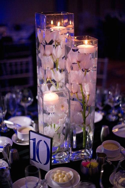Alquila tres jarrones de diferentes tamaños y rellénalos con orquídeas de seda y velas flotantes para lograr un centro simple y sencillo para tus mesas.