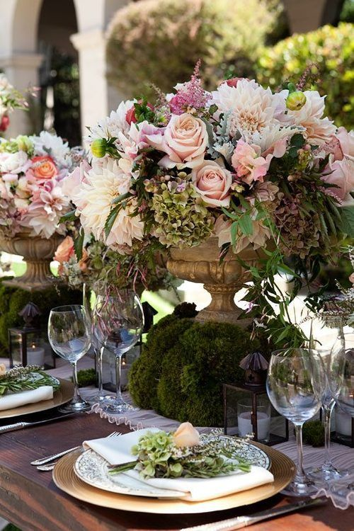 Floral centerpiece with a moss base for a garden wedding.