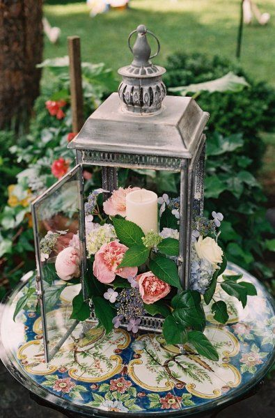 Forest-themed wedding centerpiece idea with flowers and lanterns.