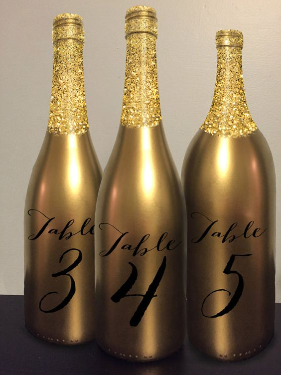 Table number and centerpiece with gold glitter wine bottles.