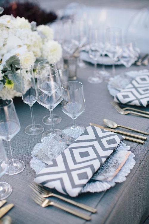 Una moderna decoración para bodas en color gris y blanco en Carolina del Norte. Servilletas con motivos en gris y blanco y menú en tonos metálicos. Foto: Millie Holloman.