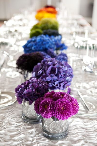 Stunningly simple rainbow flower centerpiece set against a white table.