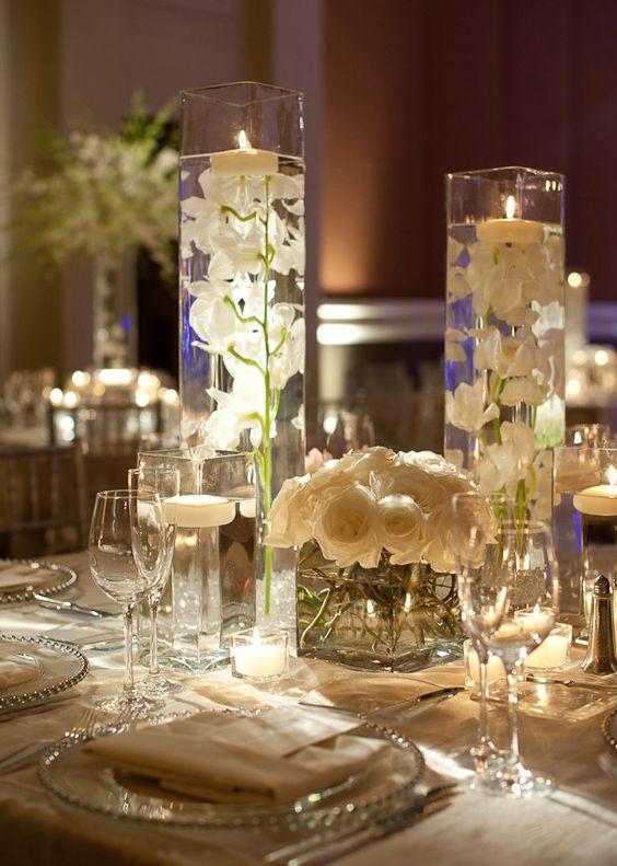 Estos fabulosos centros de mesa de vidrio o cristal le darán un look dramático a tu mesa de boda. Ideas para una recepción de bodas super chic de Edge Flowers.