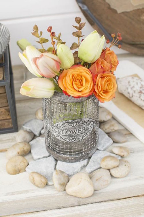 Gorgeous metal wire vases filled with tulips and sprigs for a rustic wedding.
