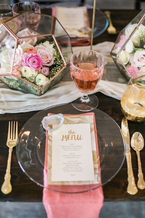 Rebanadas de geodos dorados adornan los menús de boda sobre platos transparentes en una mesa de granja decorada con un corredor de gasa y terrarios geométricos rebosantes de flores suaves. Fotografía Lori Blythe.