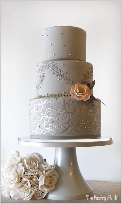 Una torta de boda muy chic en color gris y plateado con una flor en melocotón como acento.