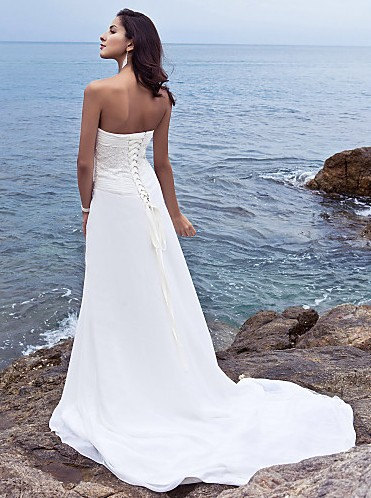 Side-draped fit and flare sheath wedding dress with beaded applique.