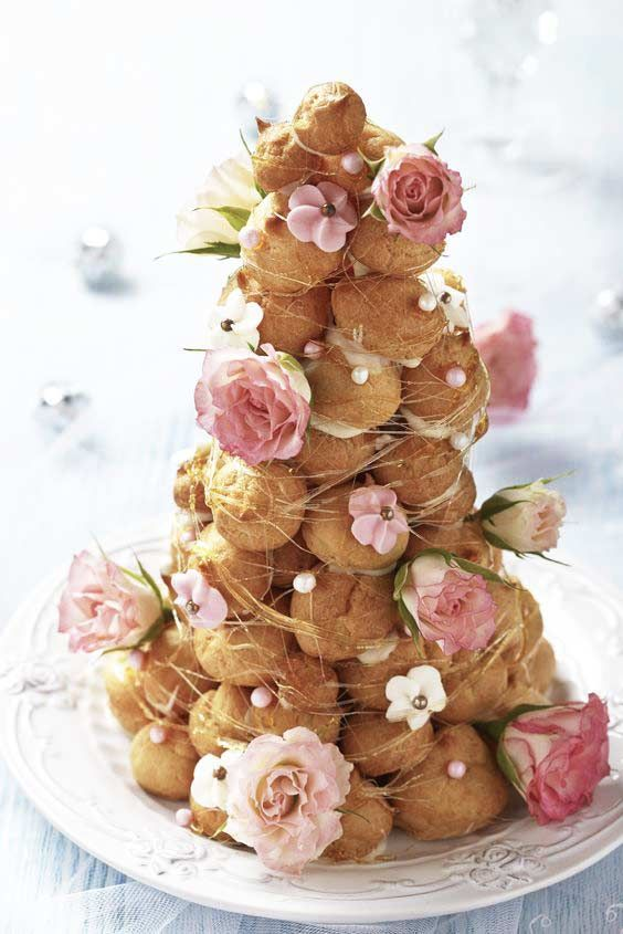 Croquembouche or tower of profiteroles with pink and white flowers for a shabby chic vintage style wedding.