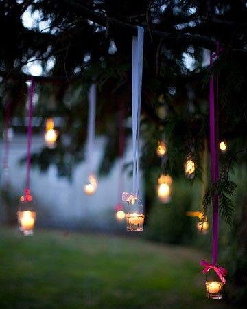 Estas velas colgadas de lazos le otorgan un look boho a una boda al aire libre.