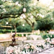A pink and grey-themed wedding at the Houston Zoo with a gray table runner trimmed with lace and pretty white flowers. Photo: Brides.