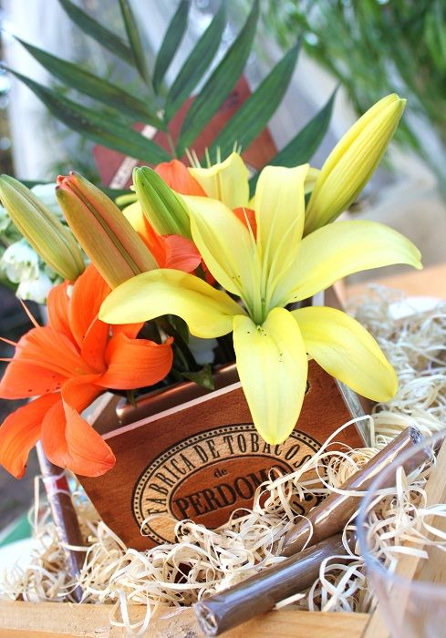 Centros de mesa con temática de noches de La Havana. Aprovecha las cajas de cigarros Cubanos para ahorrar en creativos centros de mesa con flores tropicales como las heliconias, aves del paraíso u orquídeas.