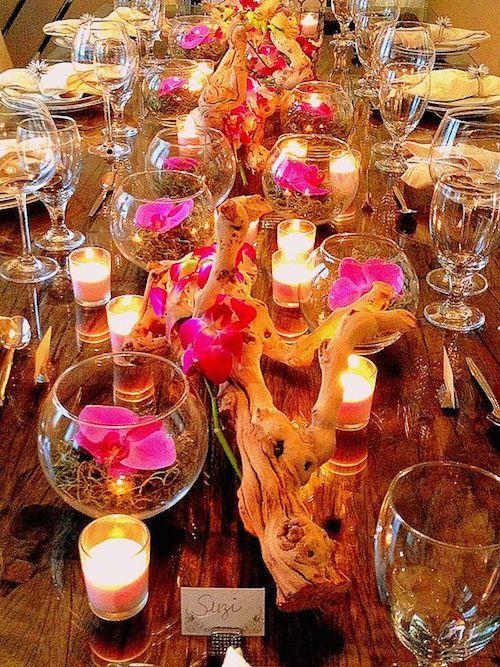 Decoración de bodas cubanas. Vasos con orquídeas sobre musgo rodeadas de ramas de manzanita y velas que se reflejan en la cristalería de la mesa de recepción.