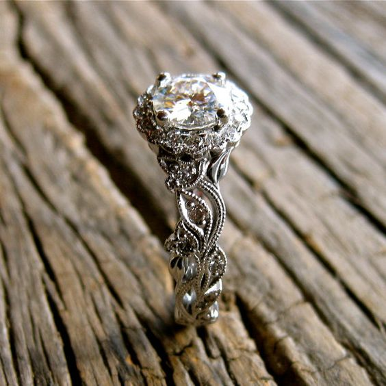 Handmade engagement ring with diamonds in flower buds and leafs on vine motif .