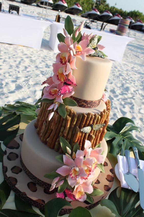 Pastel de bodas ideal para una playa adornado con flores y hojas verdes.